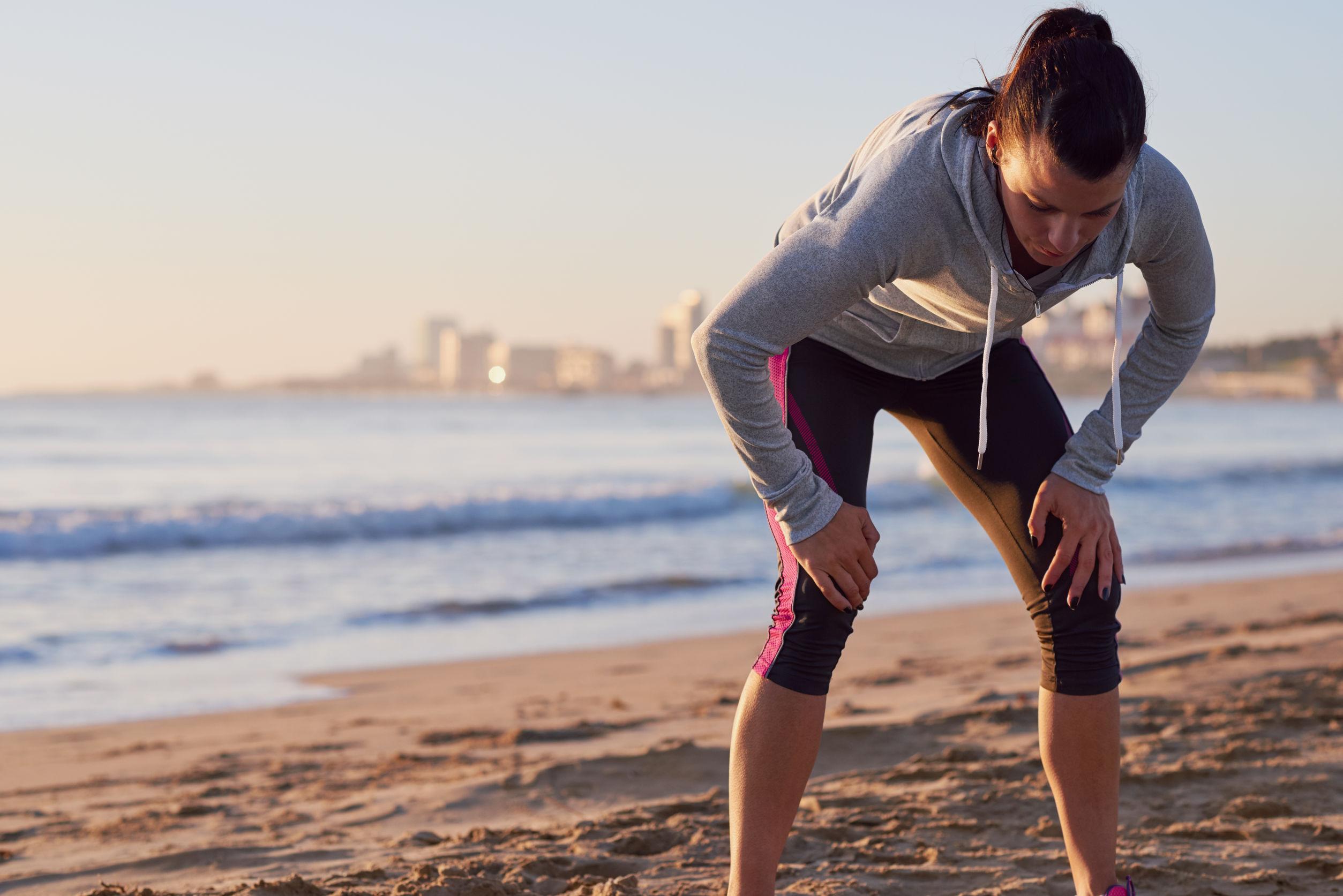 corredora agotada después de entrenamiento de fitness corriendo recuperar el aliento