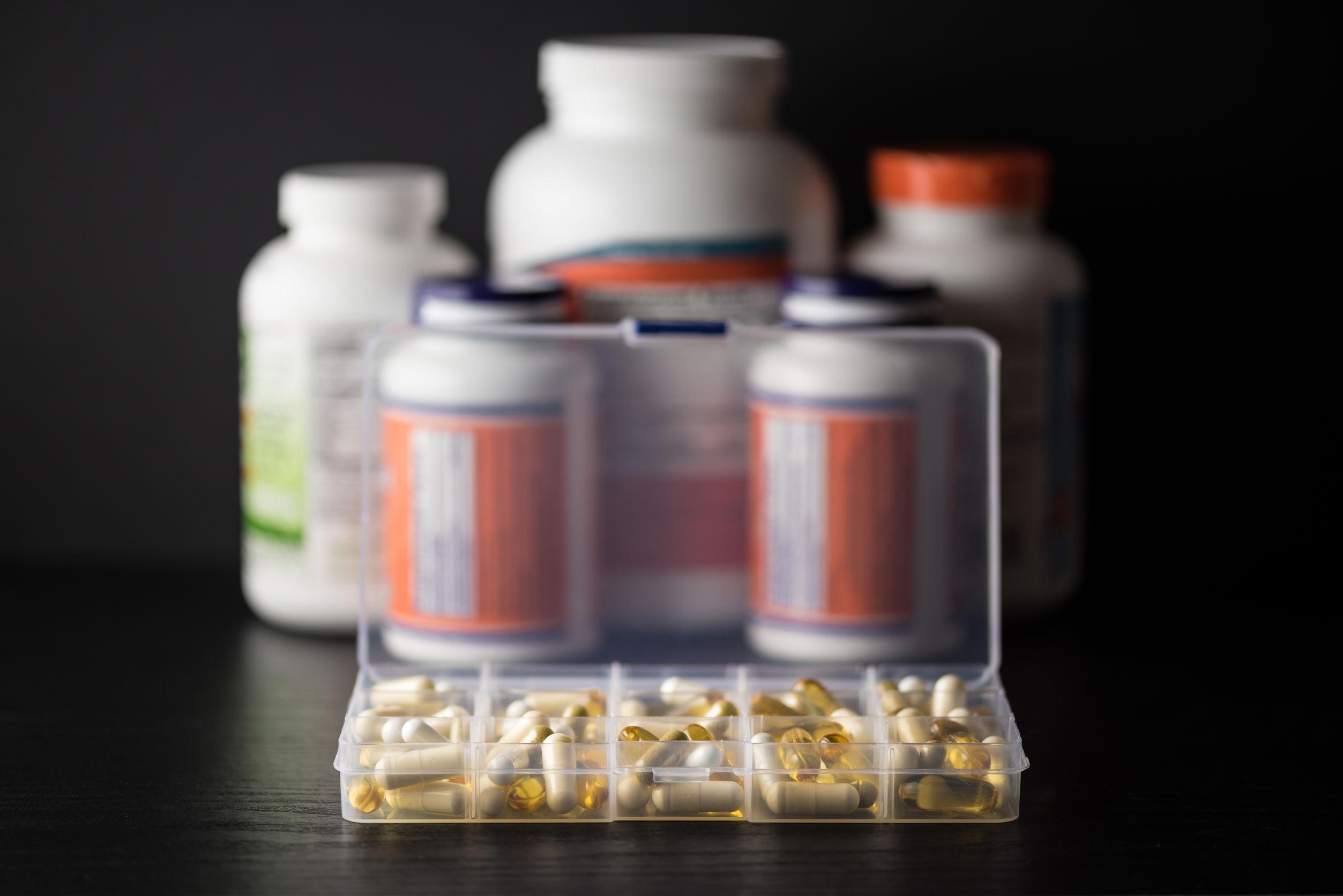 Suplementos en pastillero diario frente a cápsulas, píldoras, frascos de cápsulas blandas y tabletas, sobre mesa de madera negra con fondo oscuro.