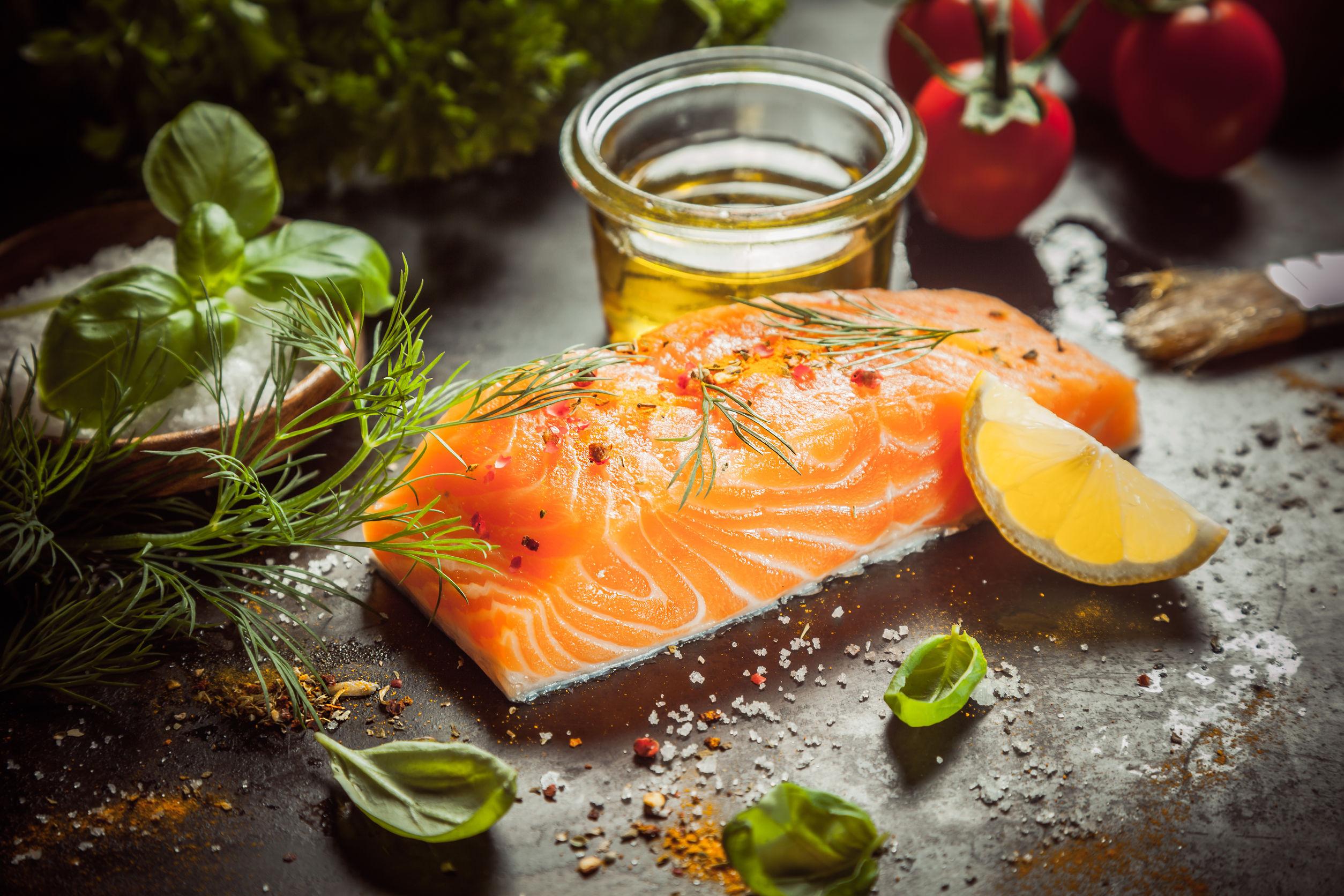 Una comida gourmet de salmón con un espeso filete de pescado suculento, aceite de oliva, hierbas, condimentos y condimentos en una encimera de cocina