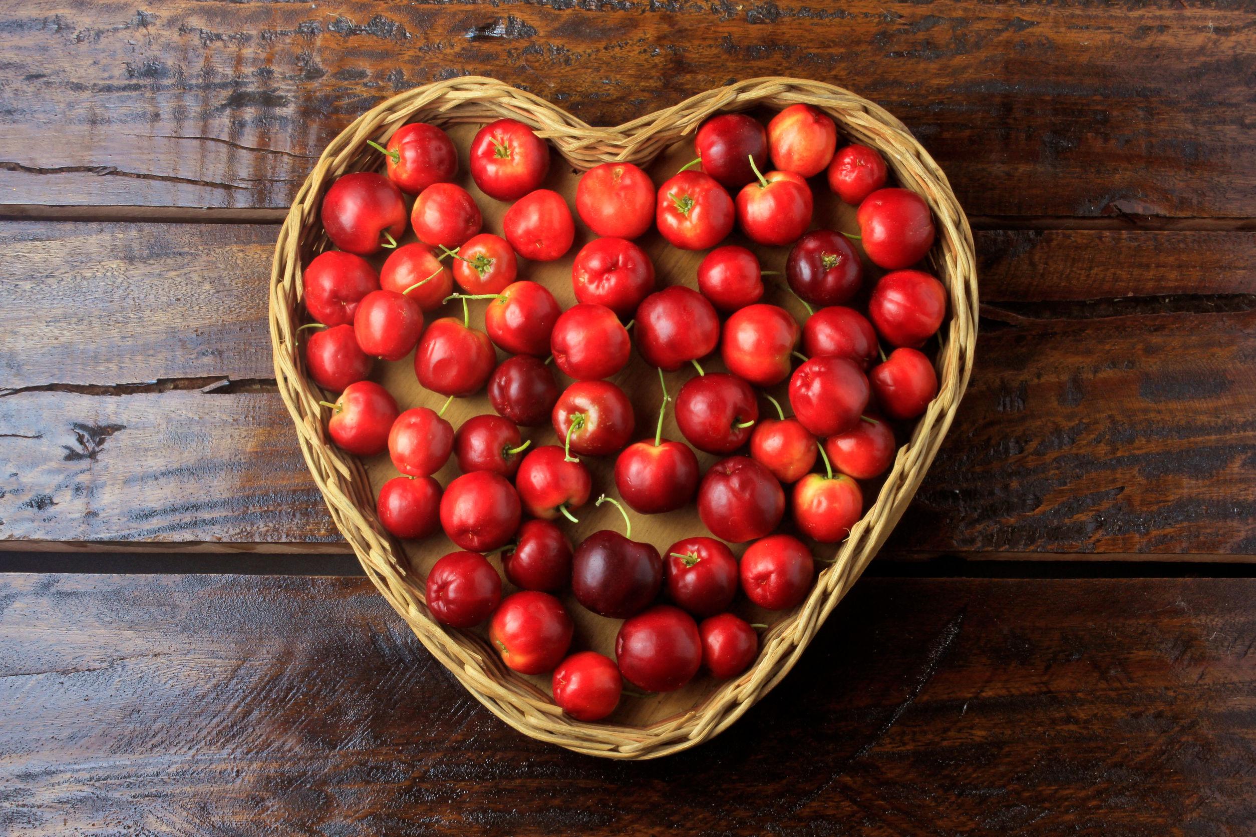 Acerola Cereza cruda, fresca, en canasta con forma de corazón sobre mesa de madera rústica, frutas antioxidantes.