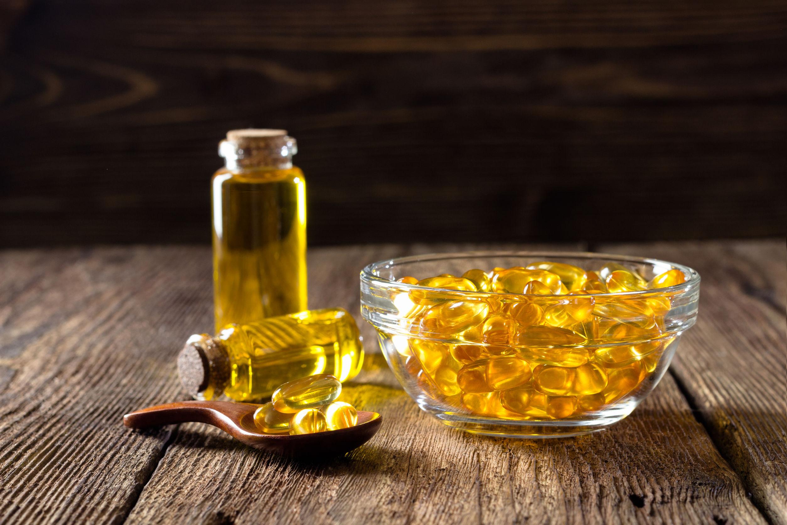 Cápsulas de aceite de pescado sobre fondo de madera