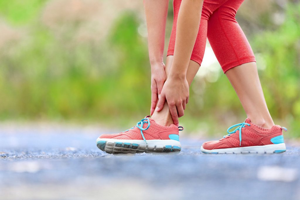 corredora tocando el pie con dolor de tobillo