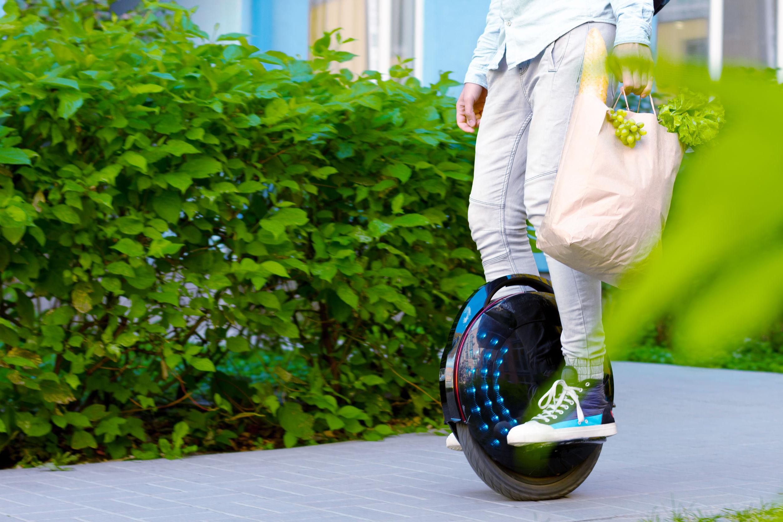 Hombre joven moderno hombre exitoso empresario autónomo con paquete de alimentos, verduras y frutas con monociclo eléctrico ecológico