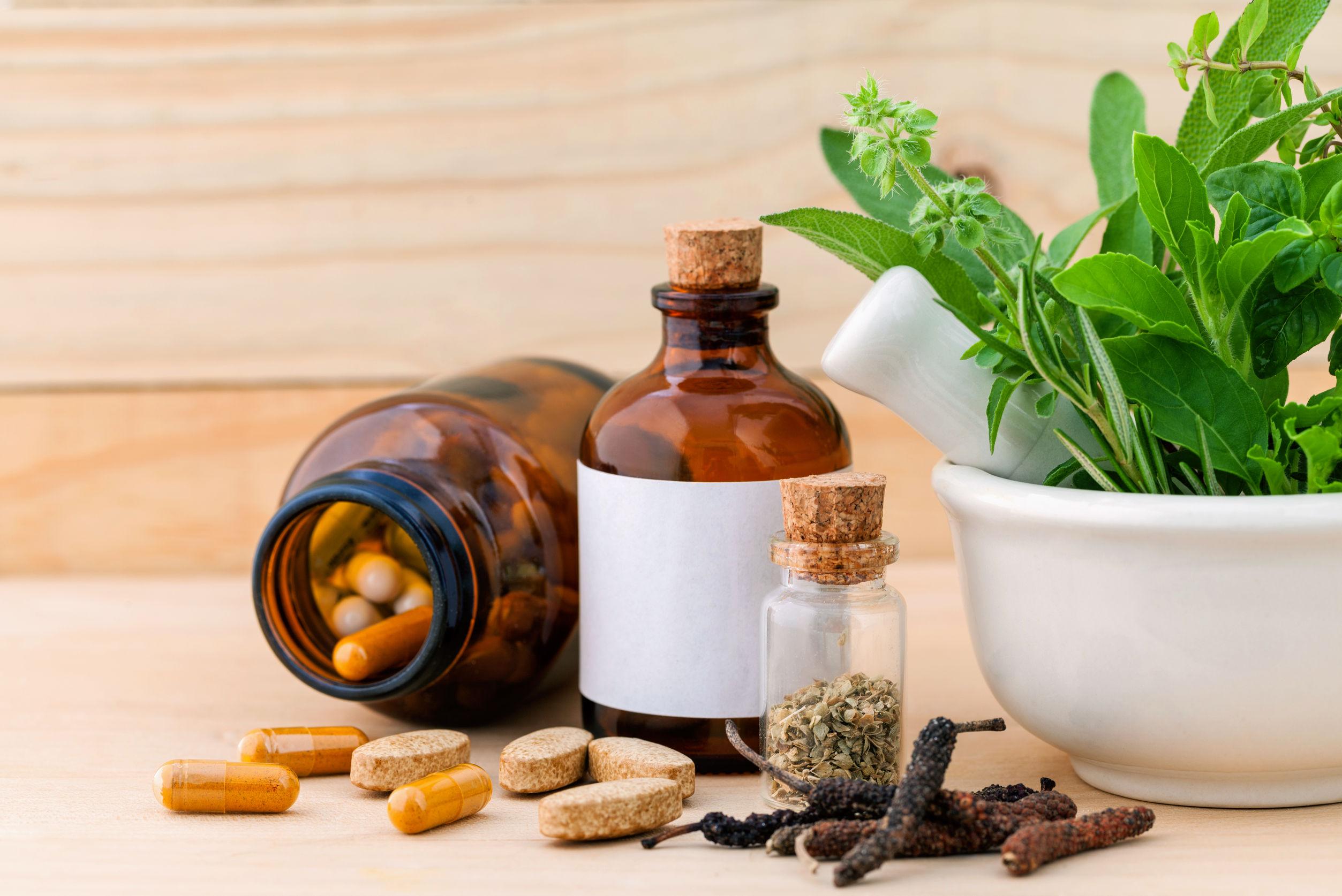 Cápsula de hierbas, secas y hierbas frescas de atención médica alternativa con mortero sobre fondo de madera.