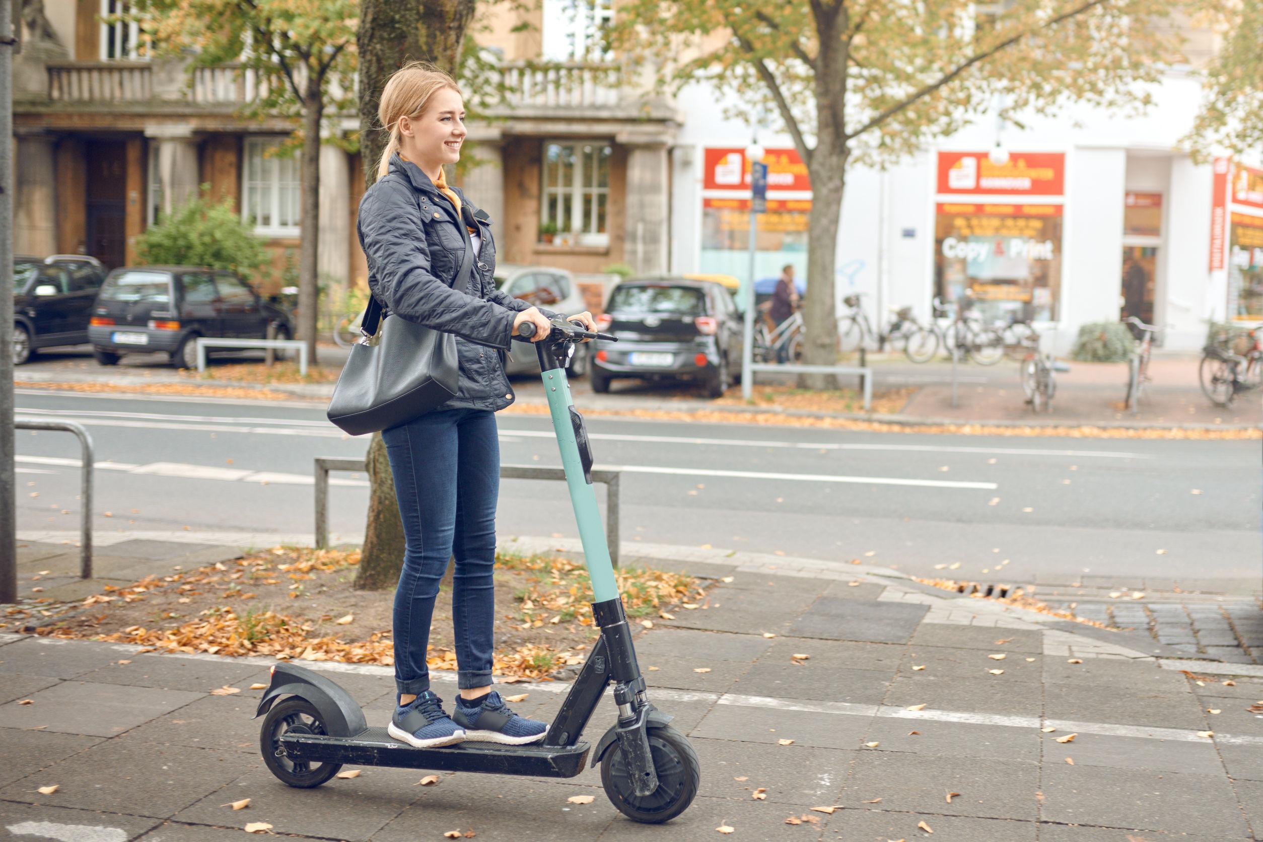 Vista lateral de joven mujer rubia feliz montando un scooter eléctrico en la ciudad en otoño