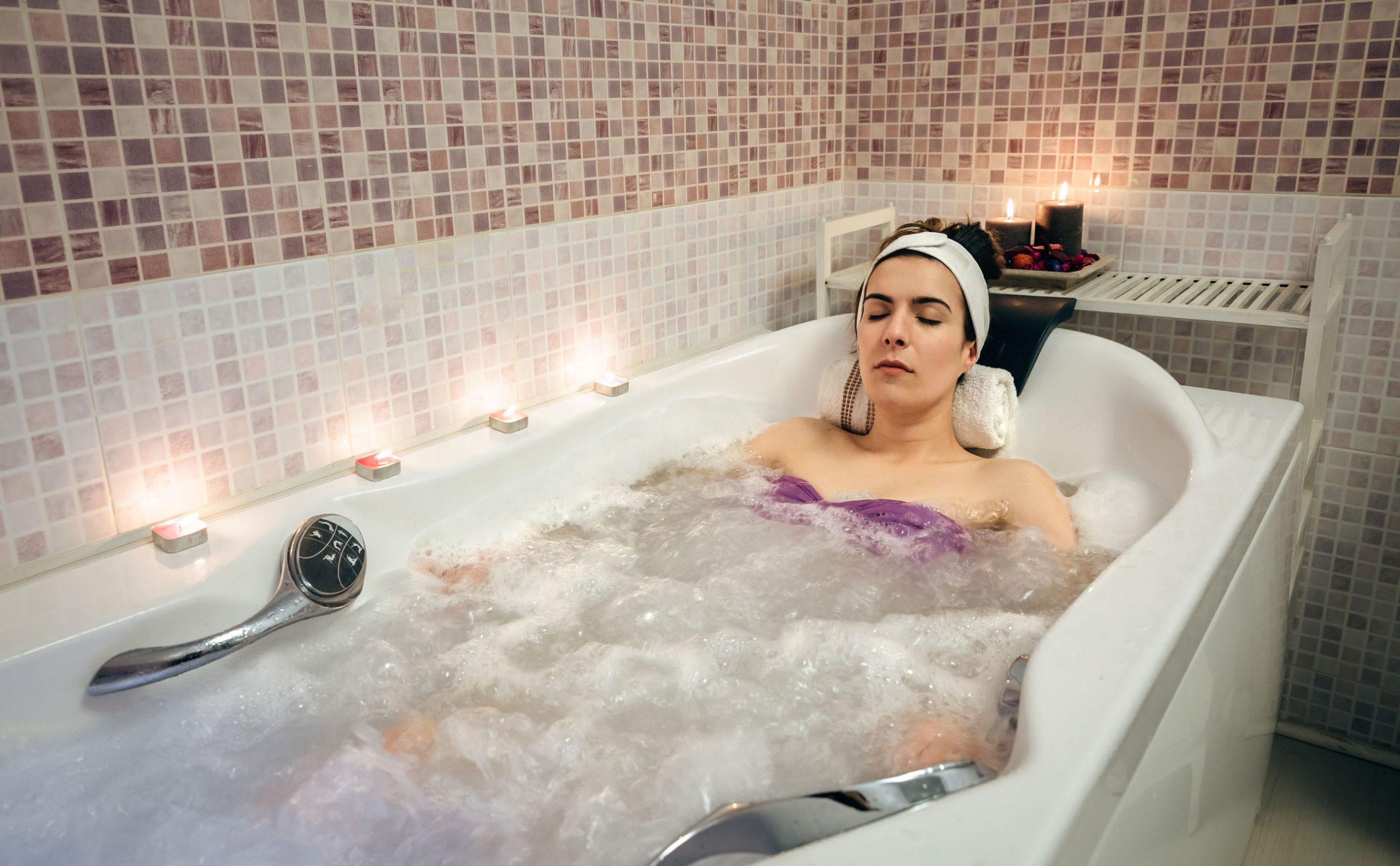 Mujer acostada en la bañera haciendo tratamiento de hidroterapia