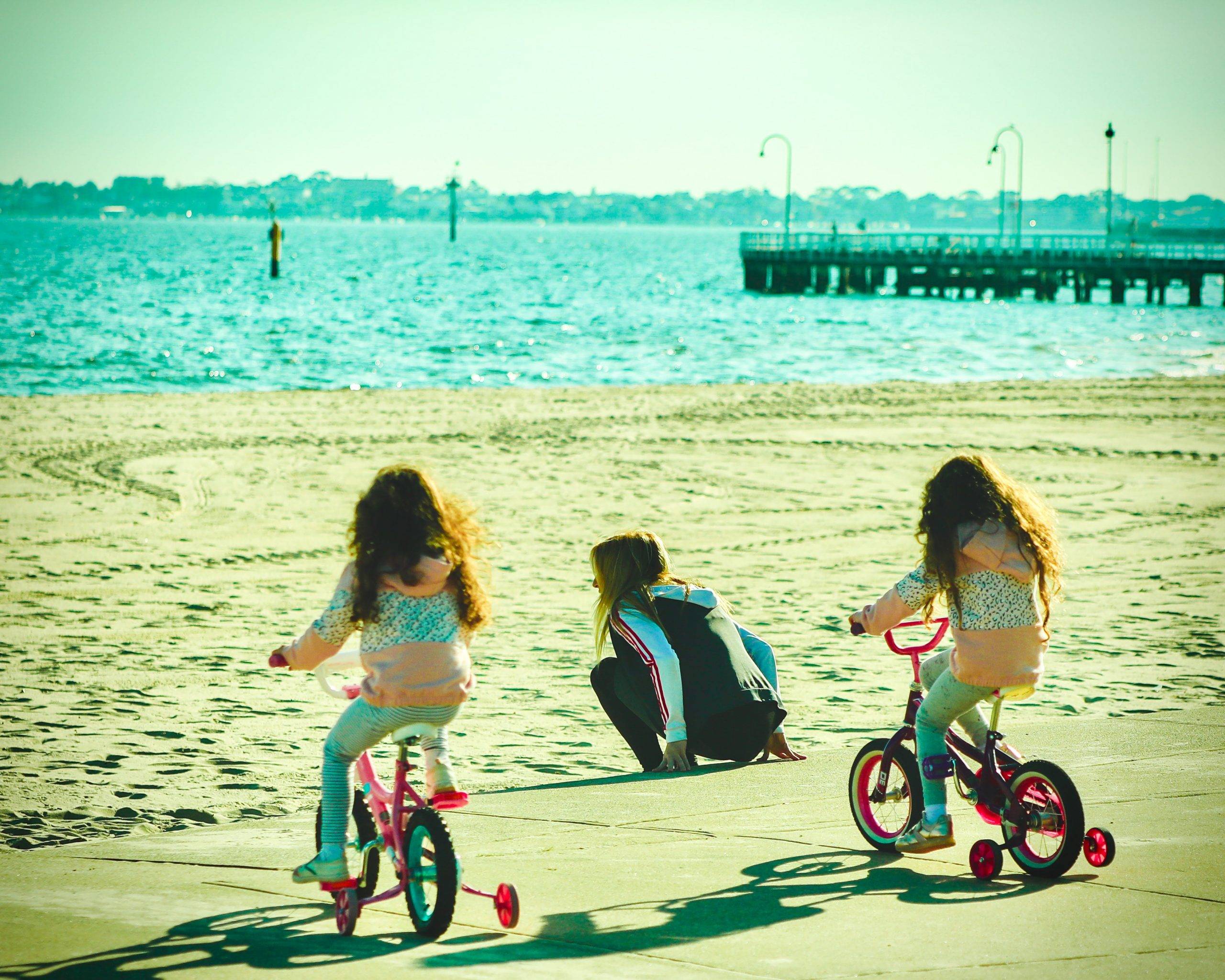 Niñas montando bicicletas con ruedas de entrenamiento.