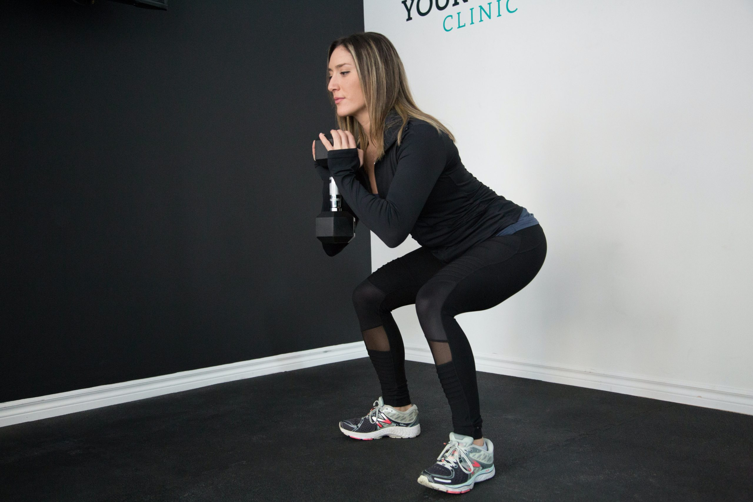 Mujer con ropa de gimnasia negra realizando sentadillas