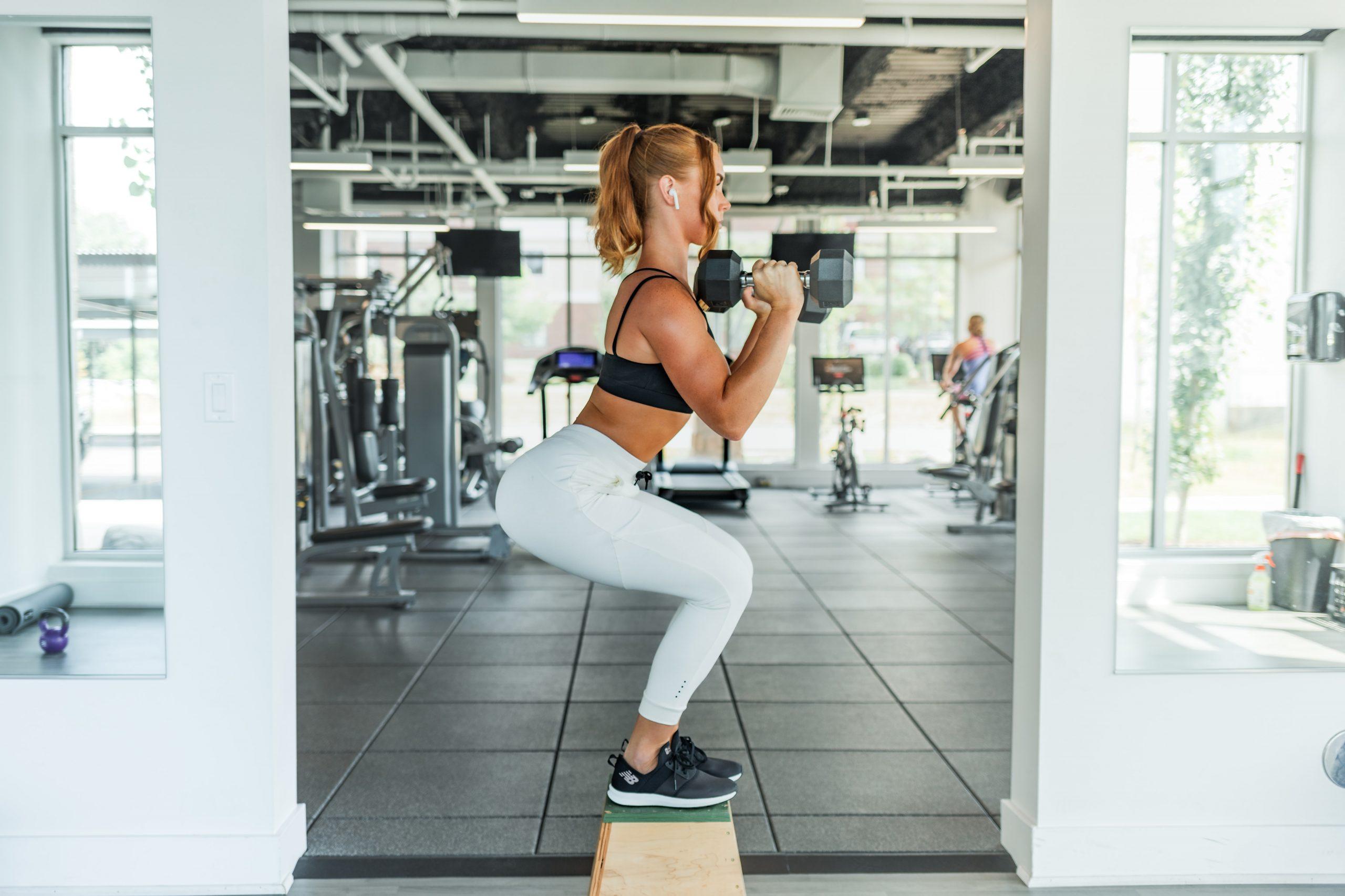 Mujer haciendo sentadillas en gimnasio