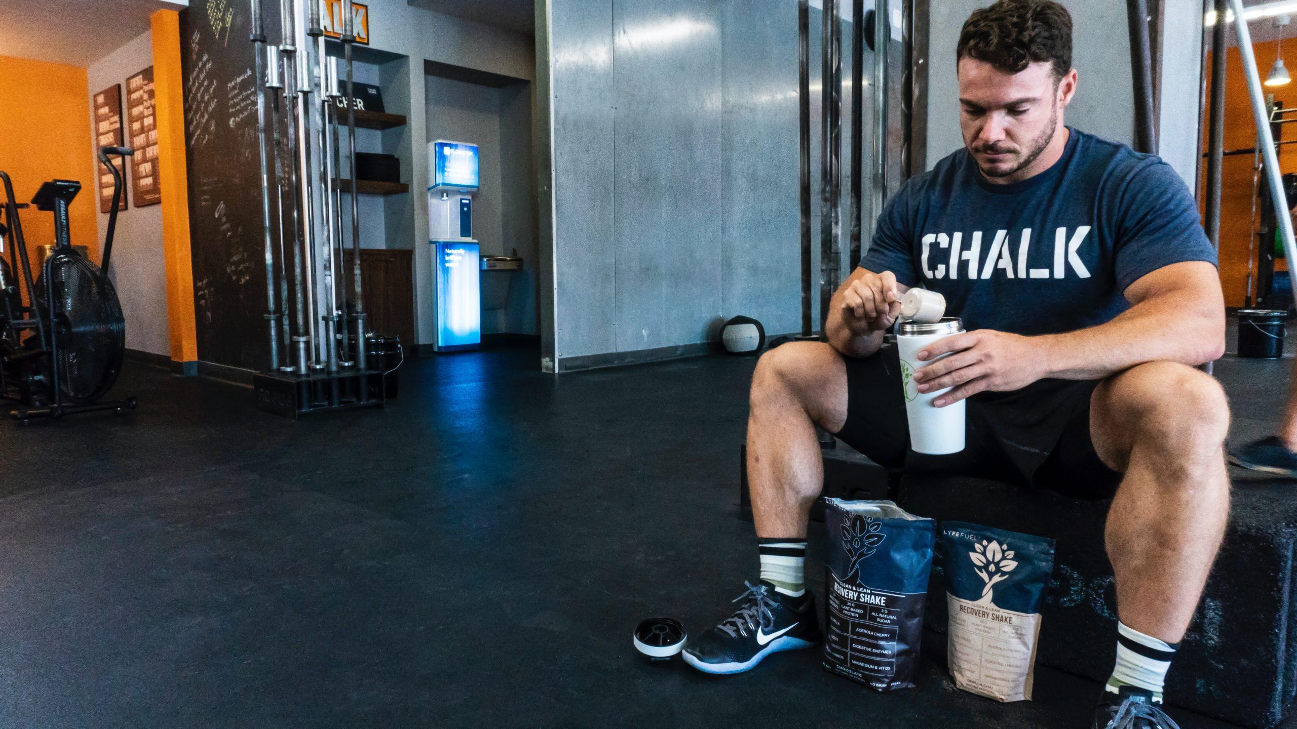 Hombre musculoso preparadose batido de proteinas