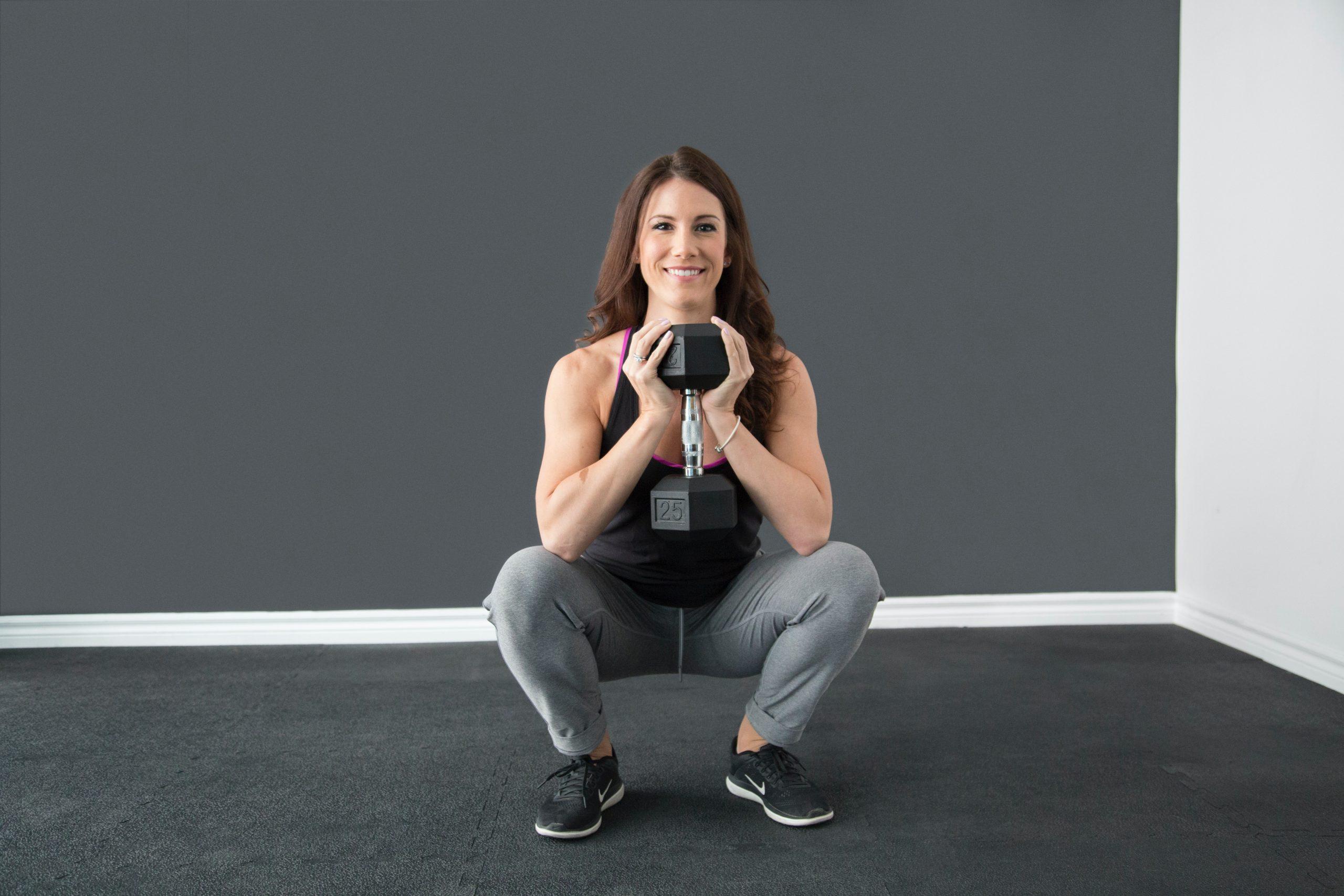 Mujer haciendo sentadillas con peso