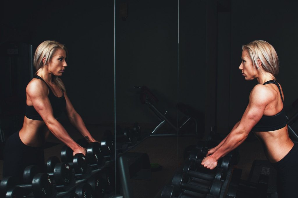 Mujer en gimnasio frente a espejo