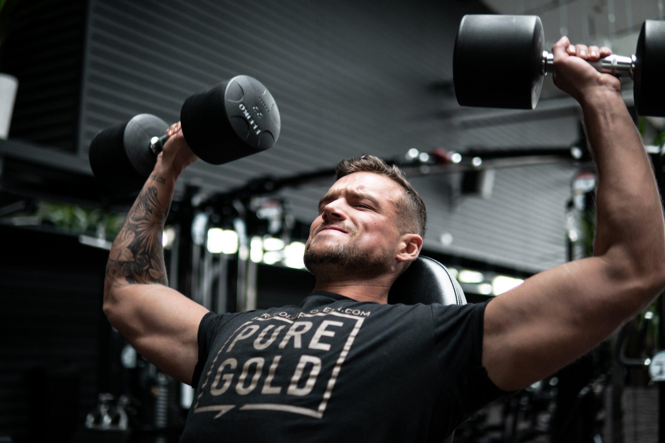 Hombre musculoso ejercitándose con mancuernas