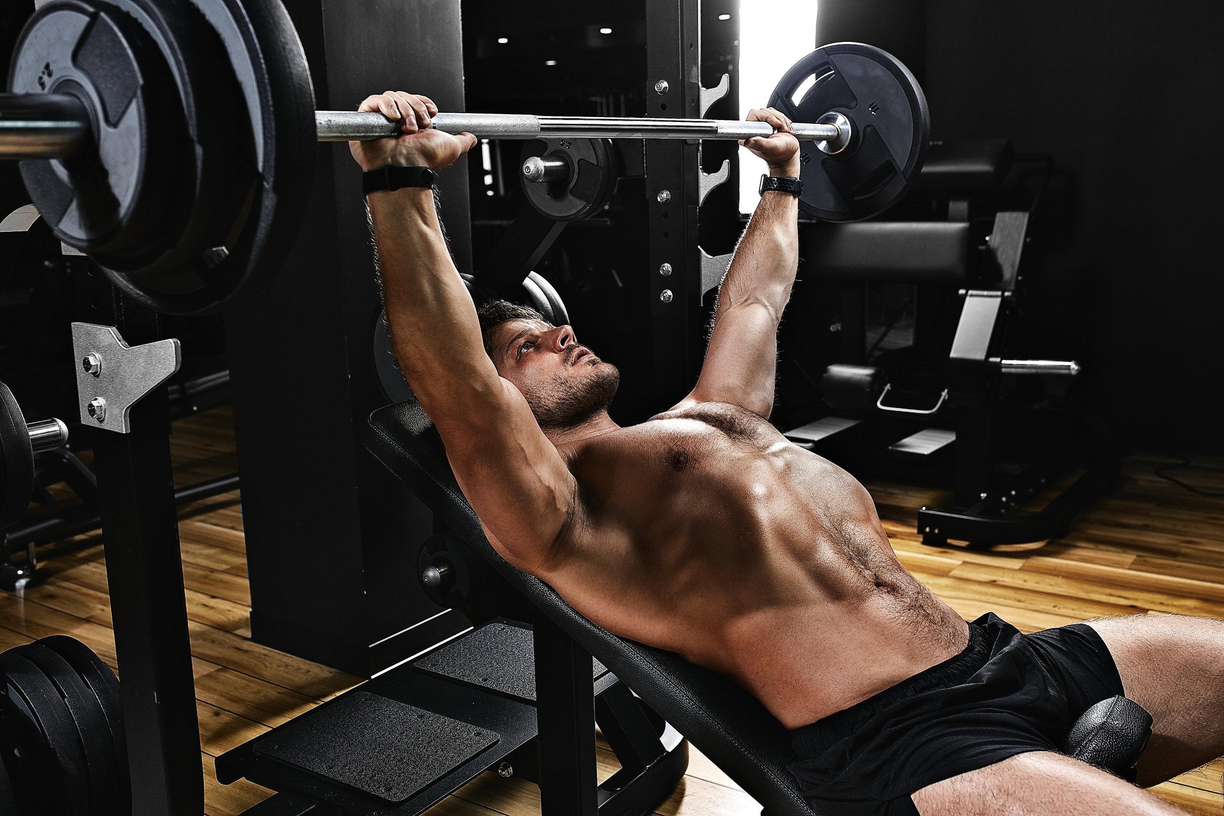 apuesto joven haciendo ejercicio de press de banca en el gimnasio