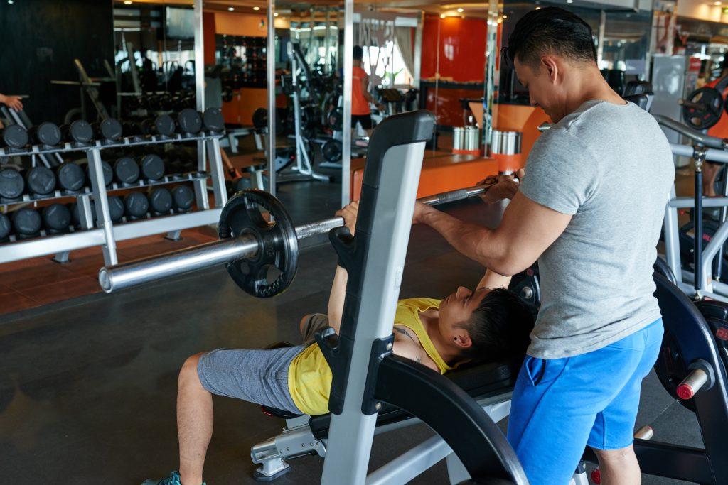 Dos jovenes en gimnasio levantando pesas