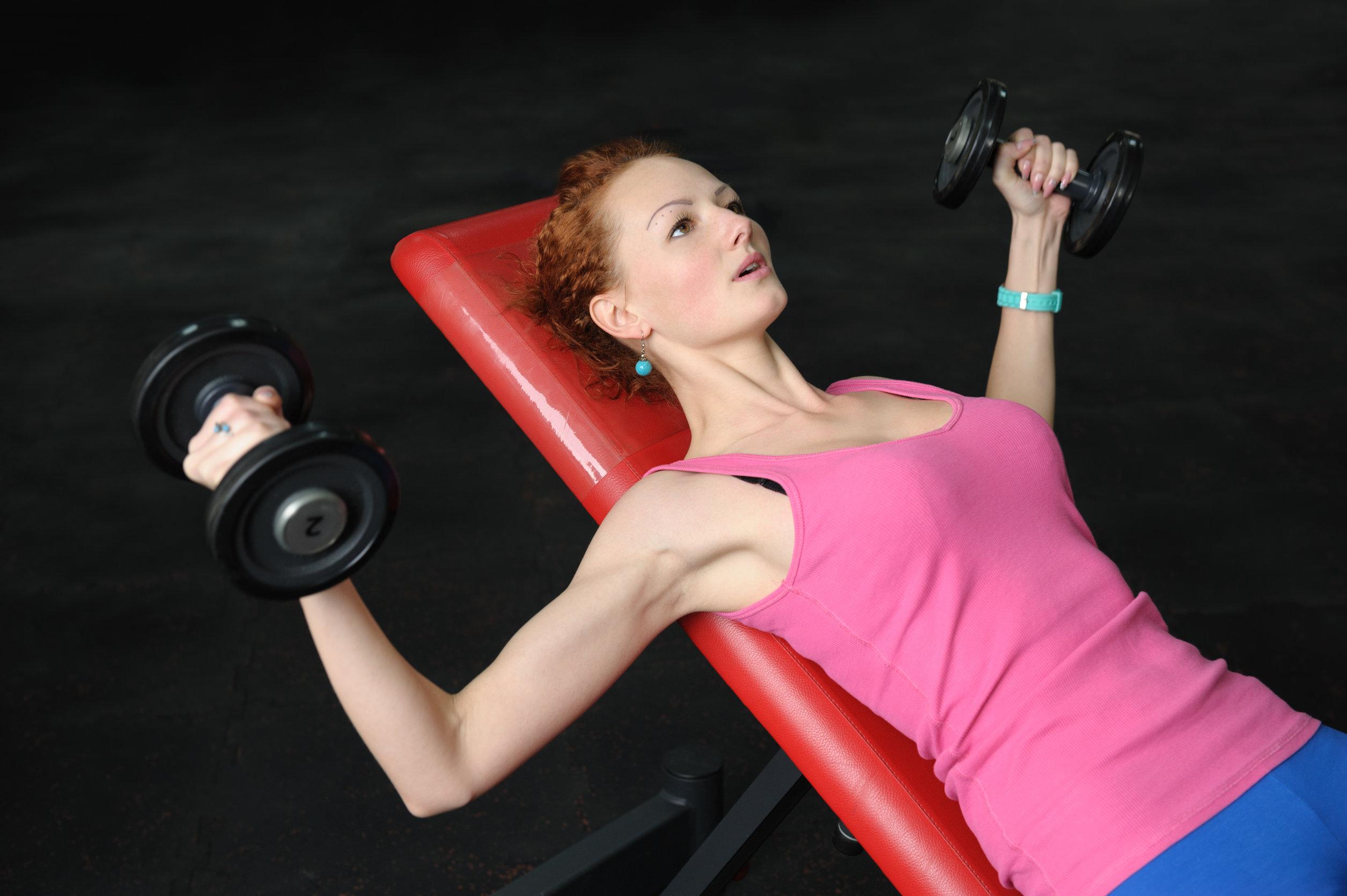 Niña haciendo mancuernas Incline Bench Press entrenamiento en gimnasia